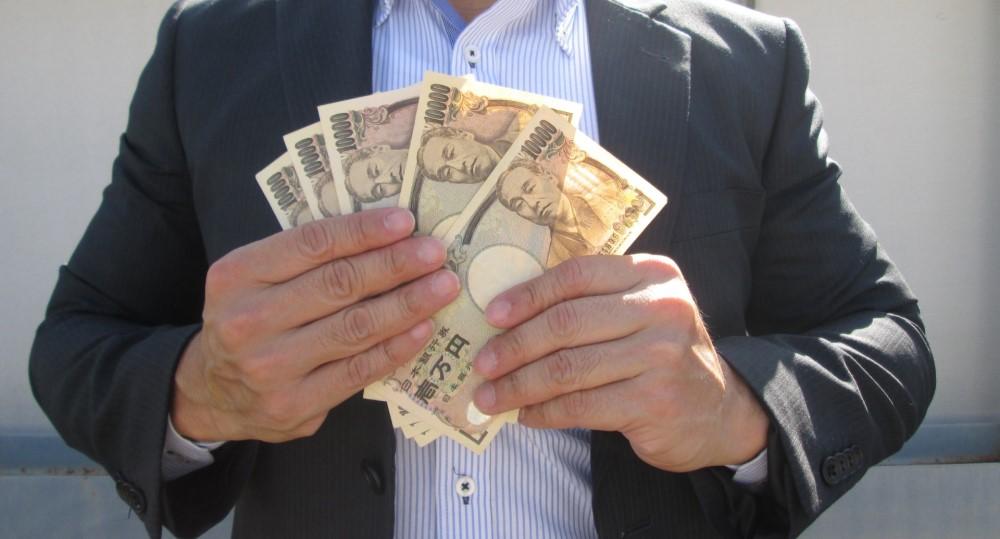 数万円を手に持つ男性サラリーマン